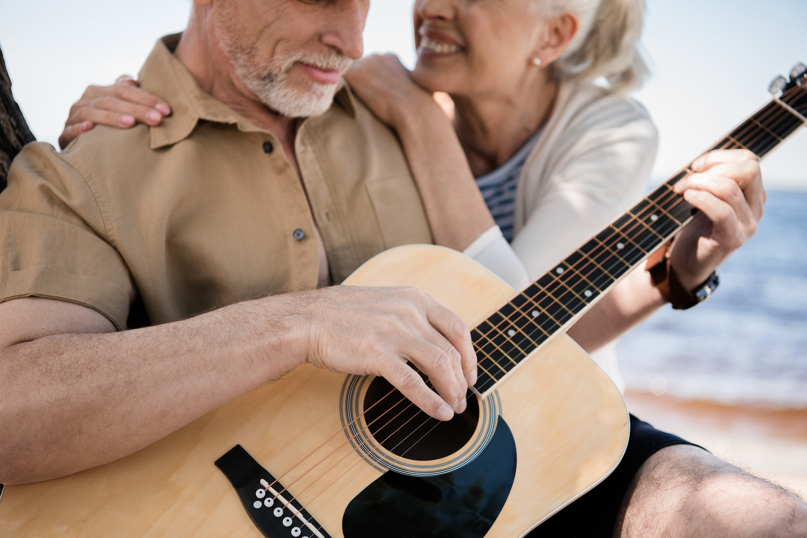Cropped shot of happy senior woman hugging bearded man playing guitar outdoors